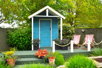 Fototapeta Wooden blue painted garden tools storage shed among green grass, potted plants and pink deckchairs in summer in the English countryside. Northamptonshire, UK obraz