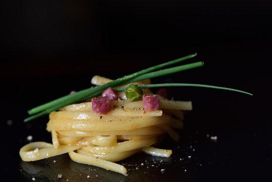 Spaghetti mit Speck und Schnittlauch dekorativ vor dunklem Hintergrund