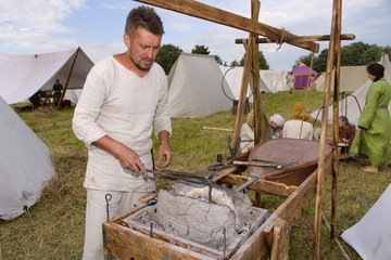 Blacksmith heats metal in a medieval horn in a field in summer
