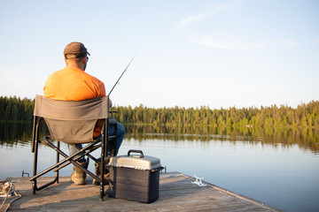 A man fishing on a lake on a wooden dock in Ontario Canada