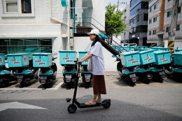 A woman on an electric scooter passes by Baemin Rider motorbikes in Seoul