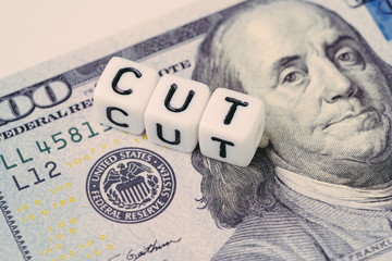 FED, Federal Reserve with interest rate cut concept, small cube block with alphabet building the word CUT next to Federal Reserve emblem on US Dollar banknote