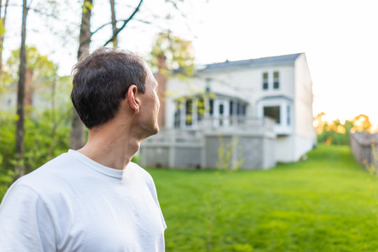 Young man homeowner in Herndon, Northern Virginia, Fairfax county residential neighborhood in spring or summer looking at house backyard
