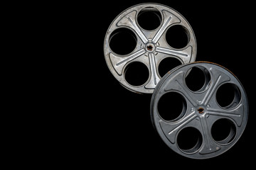 Two vintage film reels on a black background with copy space