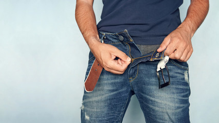 Close up shot of man in jeans with open zipper. unbuttoned blue pants