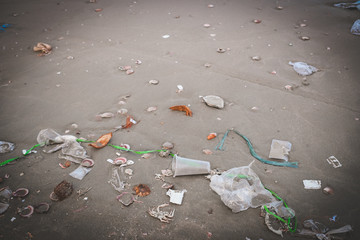 Trash, plastic, garbage, bottle, bag... environmental pollution on sandy beach. Royalty high-quality stock photo image of trash, plastic bag, bottle on the beach. Waste that polluted the ocean environ