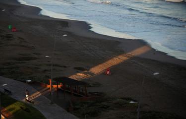 A man walks along the coastal edge on the beach of the city of La Serena