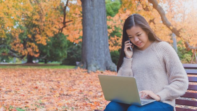 Asian beautiful smiling woman working with laptop and smartphone while sitting in garden with green grass and falling leaf in autumn.Concept of people using mobile technology.