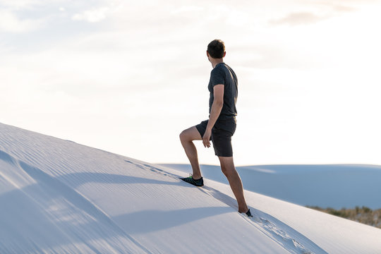 Man climbing walking on sand hill in white sands dunes national monument in New Mexico looking at sunset