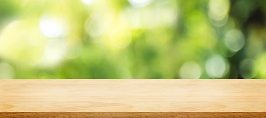 wooden plank table top with blur tree in park with bokeh light at background,Mock up template for display of your design,Banner for advertise of product