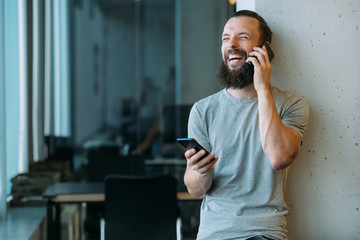 Business communication. Portrait of bearded hipster guy using two smartphones to talk and chat,...