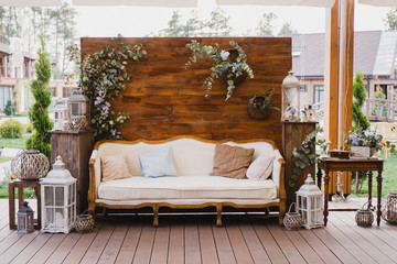 Coziness and style. Modern event design. Lounge and photo zone and european traditional wedding ceremony decoration outdoors in the restaurant before the reception. Fototapete