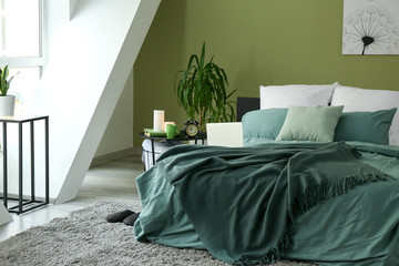 Big comfortable bed in stylish interior of room