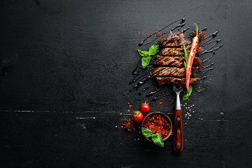 Tuinposter Steakhouse Pork steak on the fork. On a wooden background. Top view. Free space for your text.