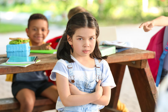 Bullied little girl with schoolmates outdoors