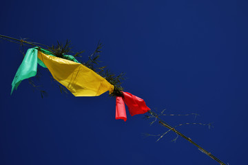 Green, yellow and red flags in blue sky, party of the street from below in brazil
