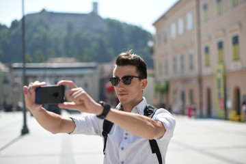 Student / tourist taking photos with smartphone in the European city