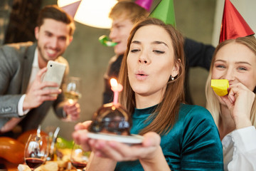 Woman blows out cake on birthday party
