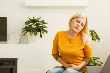 girl having period is sitting on sofa and feeling much of painful on her stomach and twist her body. Women's pain or menstrual syndrome. She holds onto her stomach and curls through spasms.