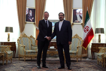 France's top diplomat Emmanuel Bonne shakes hands with Ali Shamkhani, the Secretary of the Supreme National Security Council of Iran in Tehran