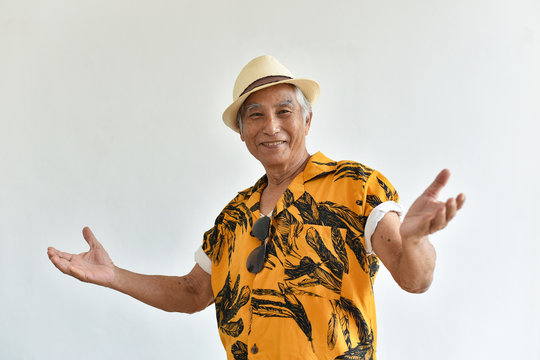 Cheerful asian senior old man, Confident and smiling elderly people with welcome gesture in colorful hawaii shirt, Happy retiree citizen and travel concept.