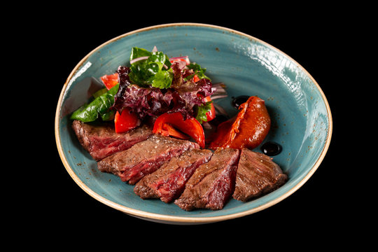 Bbq skirt steak served with griiled vegetables on a plate isolated at black background.
