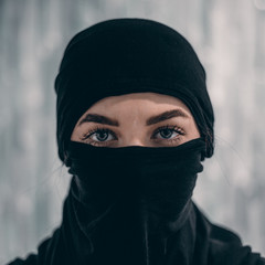 Woman portrait with deep eyes and eyelashes beauty make up, wearing black scarf niqab hijab around face and neck..