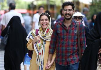 People walk in Valiasr street in Tehran