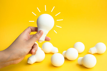 Ideas inspiration concepts with female hand holding lightbulb on pastel color background