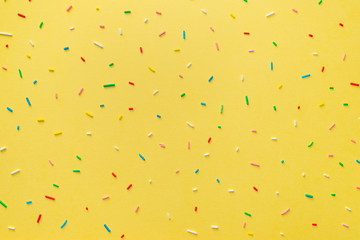 trendy pattern of colorful sprinkles over yellow background, decoration for cake and baker