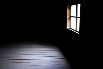 Darkness and horror, background with copy space. Inside in an empty dark room of an old abandoned house with black walls mystical light in the darkness of the window with a spot on the floor Wall mural