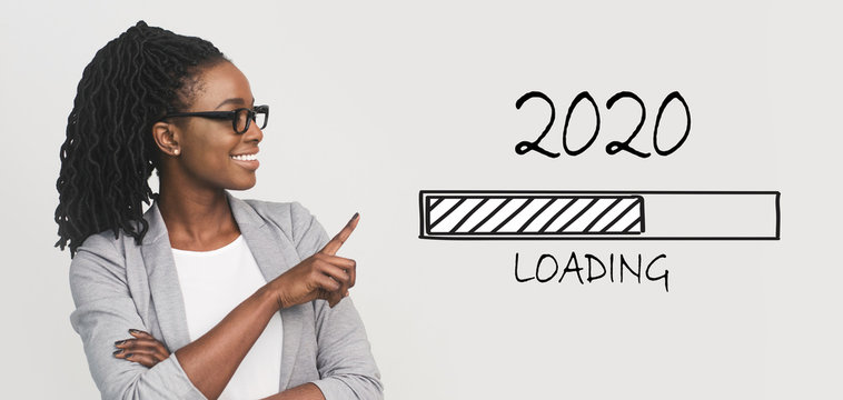 Positive african business woman pointing at 2020 loading bar