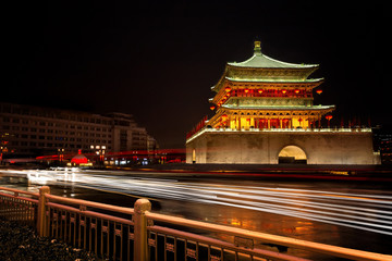 A dramatic long exposure of the Drum tower in Xian China with the lights of vehicles flowing in front.