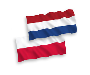 National vector fabric wave flags of Netherlands and Poland isolated on white background. 1 to 2 proportion.