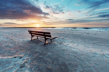 Lonely bench on the beach at sunset with view on the sea