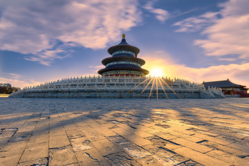 Sunrise at the Temple of Heaven, Beijing, China with a dramatic sky with clouds and the sun with sun beams appearing over a way