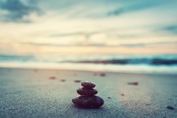 Stones pyramid on the beach at sunset. Zen