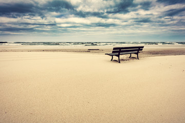 Lonely bench on the beach with view on the sea