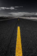 A black and white image with a yellow line in the centre in the middle of a road heading straight into the endless distance.