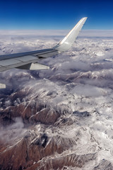 Wing of an airplane with the Himalayas below with its snow topped peaks