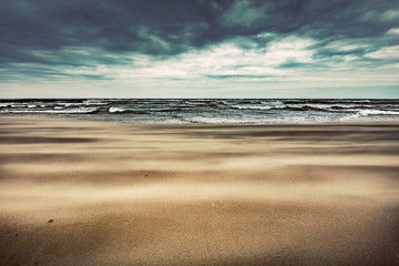 Sandy beach on stormy day by the sea.