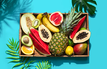 Summer healthy food concept, top down view on raw tropical fruits