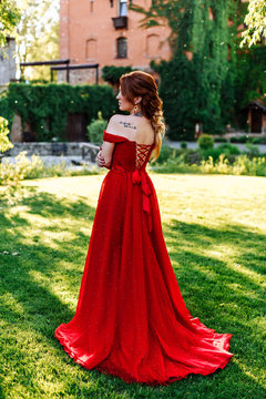Redhead woman in red dress near the castle