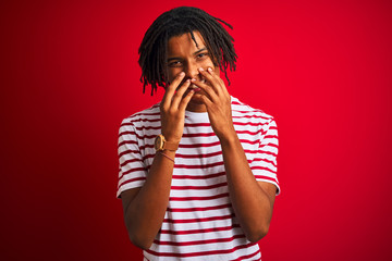 Young afro man with dreadlocks wearing striped t-shirt standing over isolated red background laughing and embarrassed giggle covering mouth with hands, gossip and scandal concept