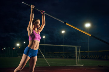 Fotobehang Gymnastiek Ready to overcome difficulties. Professional female pole vaulter training at the stadium in the evening. Practicing outdoors. Concept of sport, activity, healthy lifestyle, action, movement, motion.