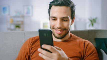 Happy Young Man Uses Smartphone while Sitting on a Sofa at Home. Man Browses Through Internet,...