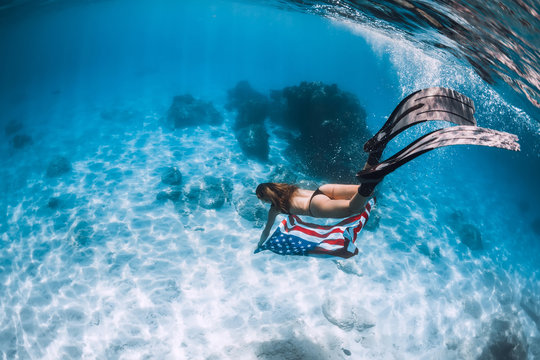 Woman freediver glides over sandy sea bottom with United States flag. Independence day.