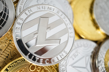 Litecoin physical coin on the stack of other different cryptocurrencies. Close-up photo of litecoin with shallow depth of field
