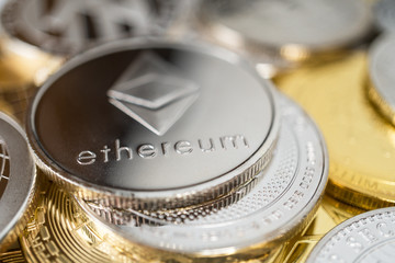 Ether physical coin on the stack of other different cryptocurrencies. Close-up photo of ether with shallow depth of field