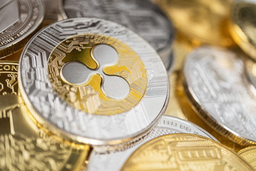 Ripple physical coin on the stack of other different cryptocurrencies. Close-up photo of ripple with shallow depth of field